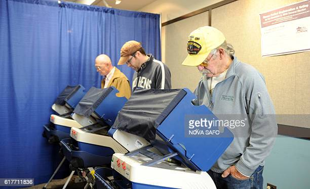 People vote at a public library in the Lincoln Park neighborhood in Chicago Illinois as early voting polling places open on October 24 2016 / AFP /...