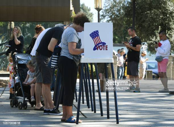 People vote at outdoor booths during early voting for the midterm elections in Pasadena California on November 3 2018