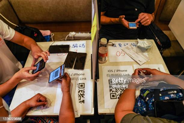 People vote inside a temporary polling station set up by a yellow economy restaurant during an unofficial primary election organized by prodemocracy...