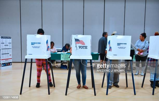 People vote inside the gymnasium of the Barack Obama Prep Academy in Los Angeles on November 6 2018 Americans started voting Tuesday in critical...