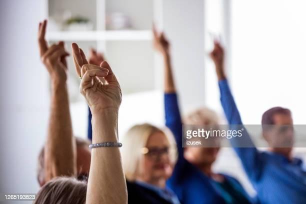 personnes votant pendant la réunion dans la maison de soins infirmiers - démocratie photos et images de collection