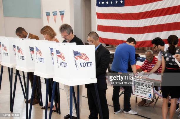 people voting in polling place - ballot box stock pictures, royalty-free photos & images