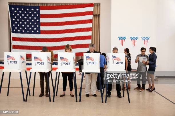 people voting in polling place - election stock pictures, royalty-free photos & images