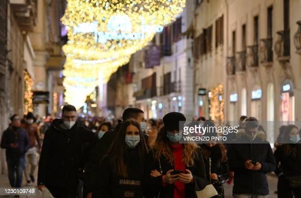 People w earing a face mask go about Via del Corso main street in central Rome, for their Christmas shopping on December 13 during the COVID-19...