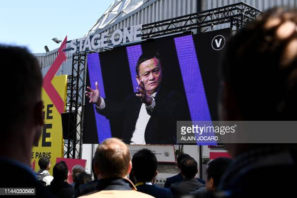 People wacth on a giant screen set outside the venue at the Paris Expo of Portes de Versaille the Chinese Alibaba group CEO Jack Ma speaking during...