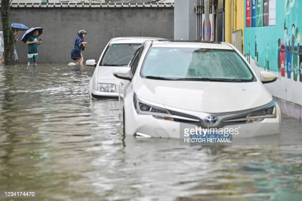 People wade in a flooded street in Ningbo, eastern China's Zhejiang province on July 25 as Typhoon In-Fa lashes the eastern coast of China.