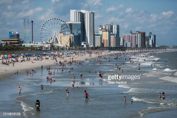 People wade in the surf on May 23 2020 in Myrtle Beach South Carolina Businesses including amusement parks have reopened for the Memorial Day holiday...