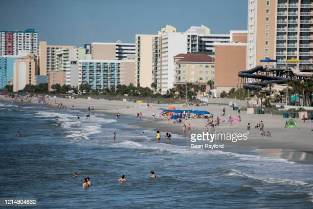 People wade in the surf on the morning of May 23 2020 in Myrtle Beach South Carolina Businesses including amusements have reopened for the Memorial...