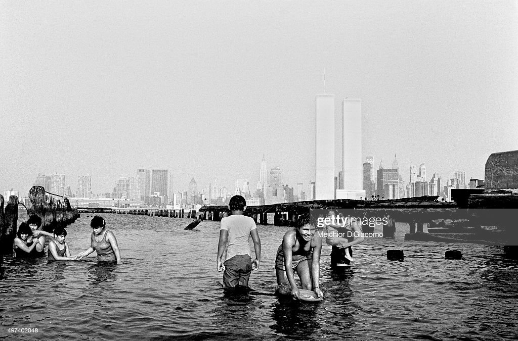 People wade in the water in front of the World Trade center seen from the Hudson river on August 1980 in JERSEY CITY, New Jersey.