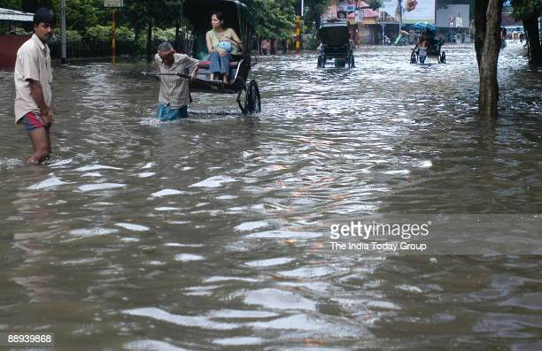 People wade through a flooded road after heavy rains and BEST bus public transport had stopped working as the less traffic on the road due to heavy...