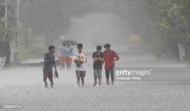 People wade through a flooded street as it rains at Kuttanad on August 20, 2018 in Alappuzha, India. In a huge relief to Keralites, rain has kept...