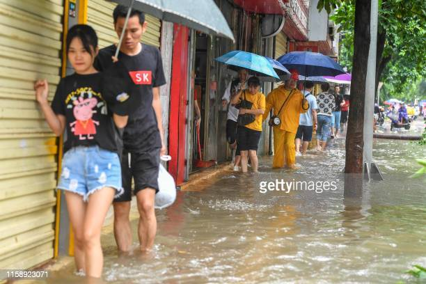 People wade through a flooded street caused by weather patterns from tropical storm Wipha in Haikou in southern China's Hainan province on August 1...