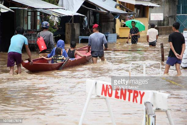 People wade through a flooded street in the town of Baao in Camarines Sur province on December 30 2018 Four people were killed in landslides and...