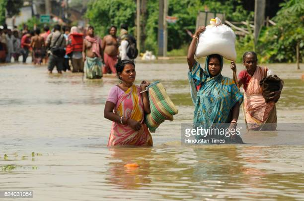 People wade through chest deep water to get to the safety in flood affected Shehagori village of Amta Block II Howrah on July 28 2017 near Kolkata...