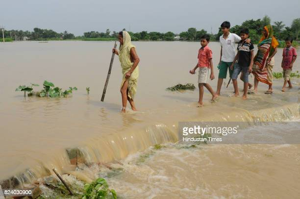 People wade through flood water to get to the safety in flood affected Chiknan village of Howrah on July 28 2017 near Kolkata India Flood situation...