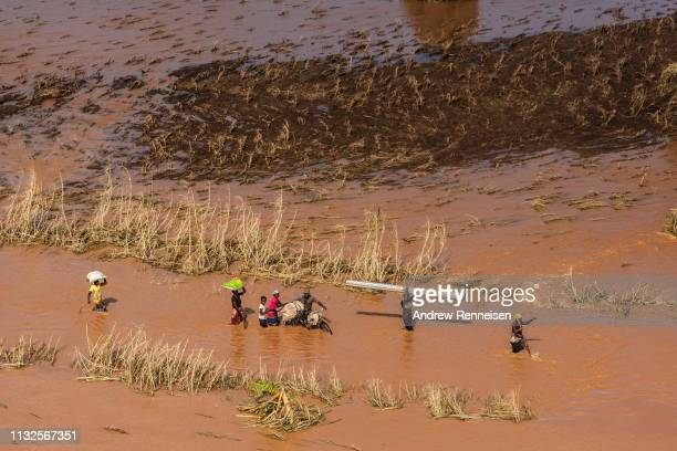 People wade through flood waters in a rural neighborhood affected by Cyclone Idai on March 24, 2019 in Buzi, Mozambique. Emergency personnel are...