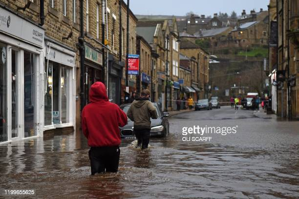 People wade through floodwater in the streets of Hebden Bridge northern England on February 9 as Storm Ciara swept over the country Britain and...