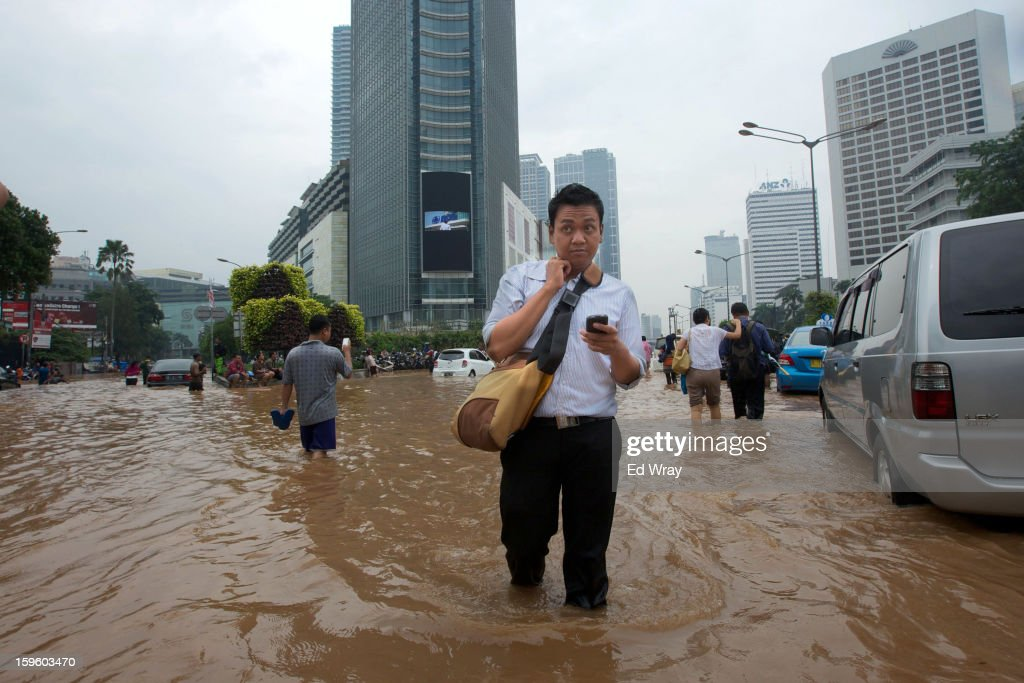 People wade through floodwaters in Jakarta's central business district on January 17, 2013 in Jakarta, Indonesia. Thousands of Indonesians were displaced and the capital was covered in many key areas in over a meter of water after days of heavy rain.