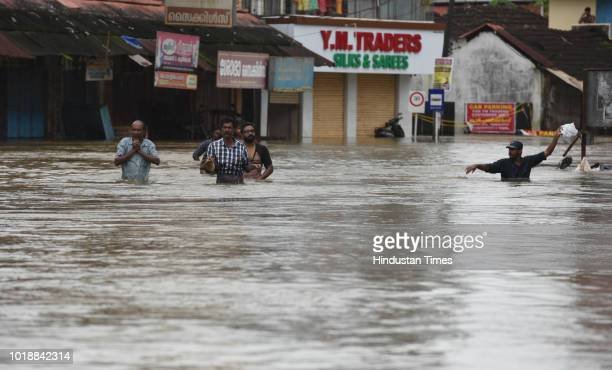 People wade through the chest deep flood water to their marooned houses at Panadala on August 18 2018 in district Pathanamthitta India The flooding...