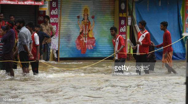 People wade through the flood waters to their marooned houses at Panadala on August 18 2018 in district Pathanamthitta India The flooding described...