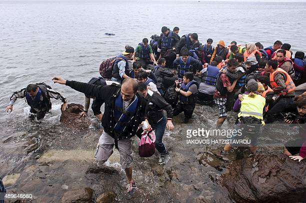 People wade through the water after getting off an inflatable boat onto the shore as migrants and refugees arrive under the rain on Sykamia beach...