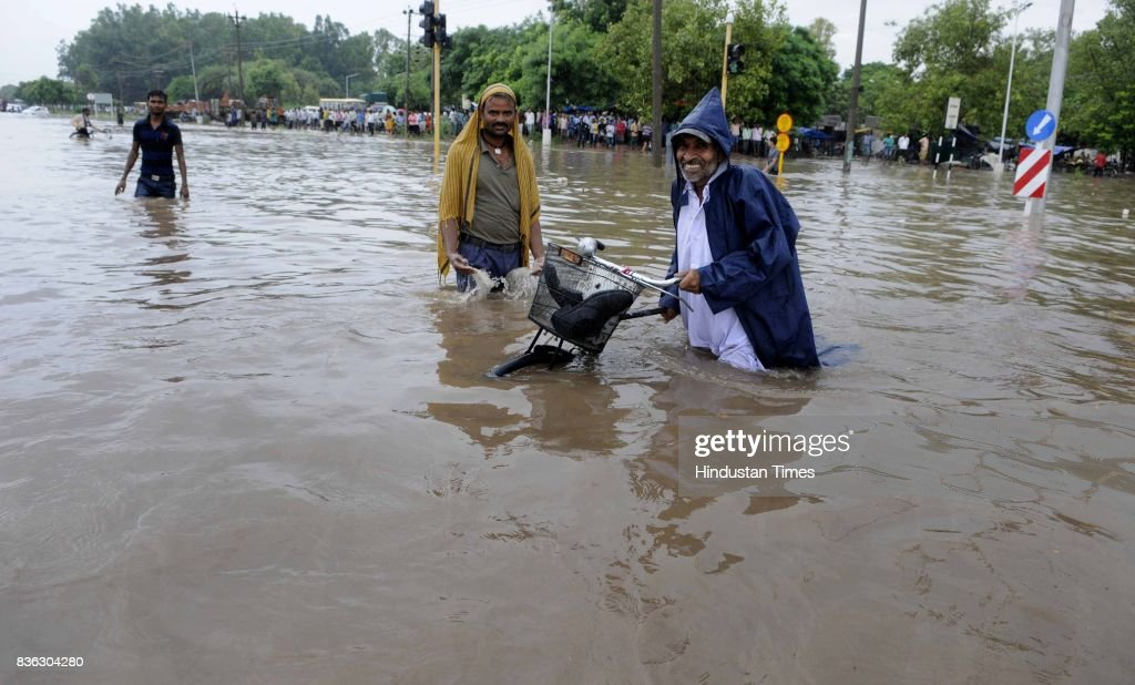 People wade through thigh deep waterlogged street at 4550 light point due to rain on August 21 2017 in Chandigarh India Heavy rainfall on morning...