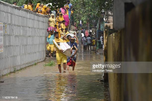 People wade through water after the Yamuna River breached the banks and entered houses and residential areas along the Yamuna Ghat at Kashmiri Gate...