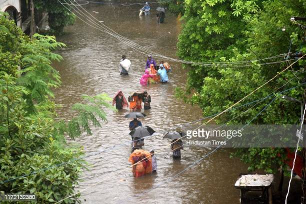 People wade through water to safety in Bahadurpur following heavy rainfall on September 29 2019 in Patna India At least 25 people were killed in...