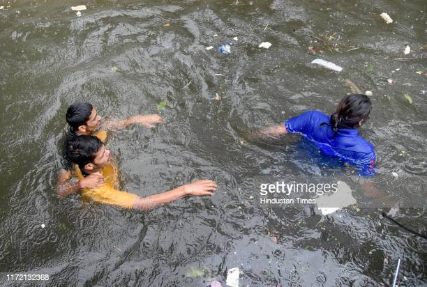 People wade through water to safety in Rajendra Nagar following heavy rainfall on September 29 2019 in Patna India At least 25 people were killed in...