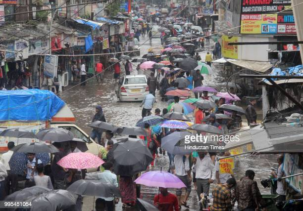 People wade through waterlogged on streets after heavy rainfall at Dadar on July 9 2018 in Mumbai India Indias financial capital and its surrounding...