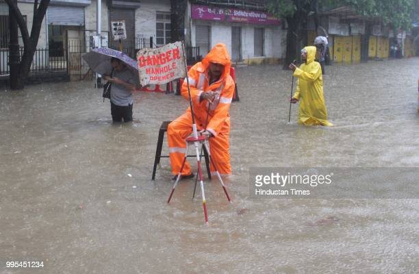 People wade through waterlogged on streets after heavy rainfall at Parel on July 9 2018 in Mumbai India Indias financial capital and its surrounding...