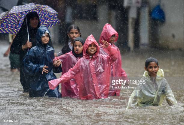 People wades through a water logged street as it rains at Sion on July 9 2018 in Mumbai India Indias financial capital and its surrounding districts...