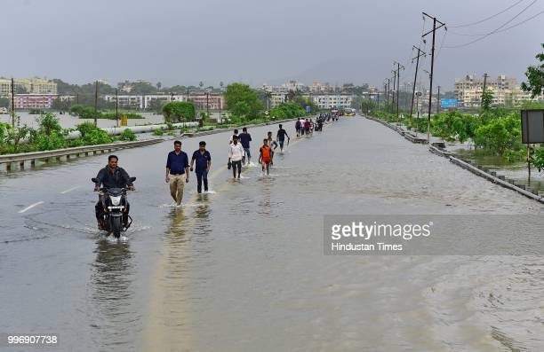 People wades through a water logged street at Ambadi Road Vasai East on July 11 2018 in Mumbai India Heavy rains made a comeback in Mumbai causing...