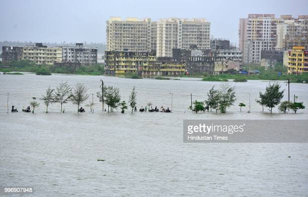 People wades through a water logged street at Evershine Nager Vasai East on July 11 2018 in Mumbai India Heavy rains made a comeback in Mumbai...