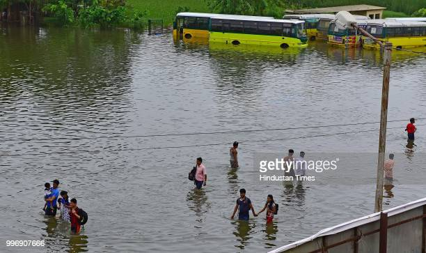People wades through a water logged street at Nallasopara West Station Road on July 11 2018 in Mumbai India Heavy rains made a comeback in Mumbai...