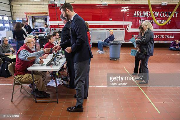 People wait a the check in desk before voting in the 2016 election at Fire Station 10 on November 8, 2016 in Arlington, Virginia. Americans across...