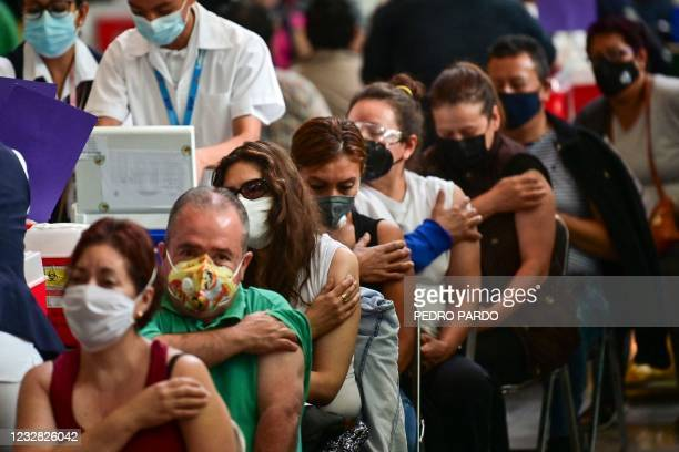 People wait after receiving doses of the Pfizer-BioNTech vaccine against COVID-19 at a vaccination center for people over 50 years old set up at the...