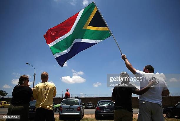People wait alongside the road to see a military plane take off from Waterkloof military airbase that is carrying the casket of former South African...