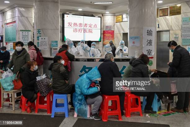 TOPSHOT People wait as medical staff wear protective clothing to help stop the spread of a deadly virus which began in the city at Wuhan Red Cross...