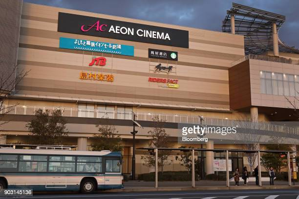 People wait at a bus stop in front of an Aeon shopping mall operated by Aeon Mall Co a unit of Aeon Co in Chiba Chiba Prefecture Japan on Tuesday Jan...