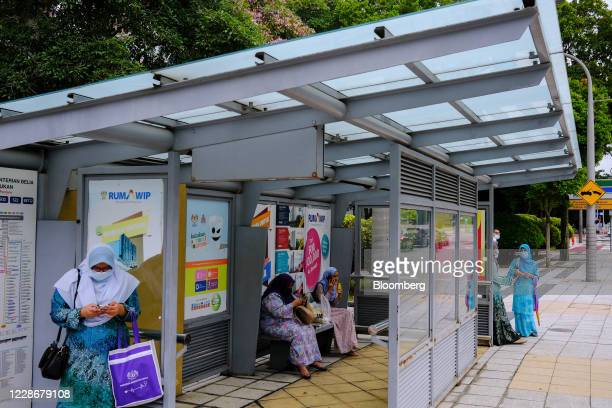 People wait at a bus stop in Putrajaya Malaysia on Wednesday Sept 23 2020 Malaysia's Prime Minister Muhyiddin Yassin urged people to reject moves to...