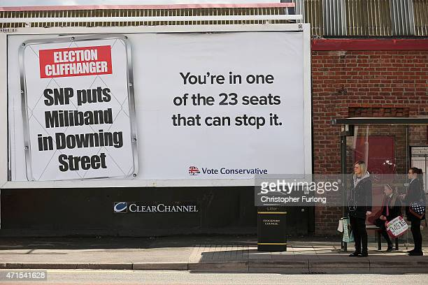 People wait at a bus stop next to an election poster by the Conservative party on April 29 2015 in Stockport United Kingdom