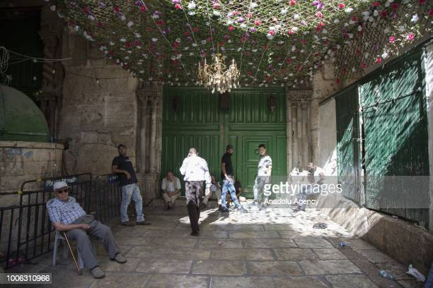 People wait at a gate of AlAqsa Mosque following its closure by Israel forces after clashes erupted between Israeli forces and worshipers on July 27...