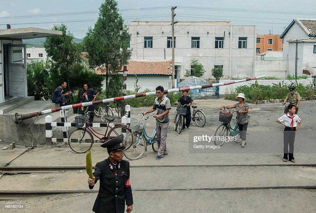 People wait at a railway crossing on August 24, 2015, North Korea. North and South Korea today came to an agreement to ease tensions following an exchange of artillery fire at the demilitarized border last week.