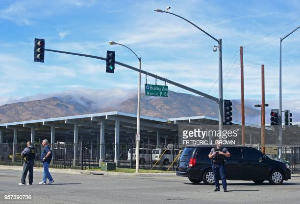 People wait at an intersection May 11 2018 following reports of shooting at Highland High School in Palmdale 40 miles north of downtown Los Angeles...