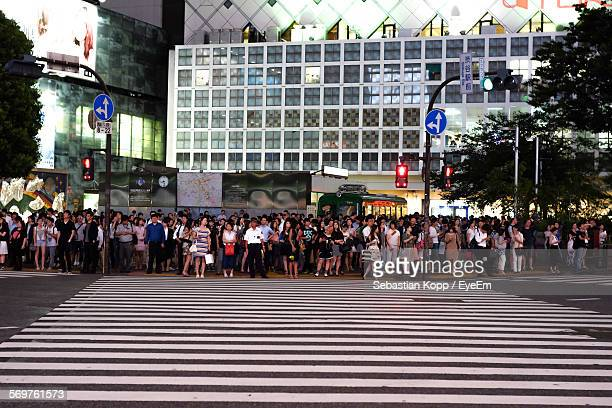 people wait at pedestrian crossing in city - road signal stock pictures, royalty-free photos & images