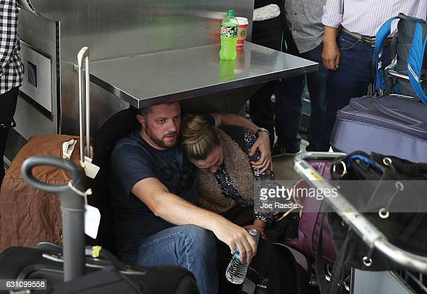 People wait at the Fort LauderdaleHollywood International airport after a shooting took place near the baggage claim on January 6 2017 in Fort...