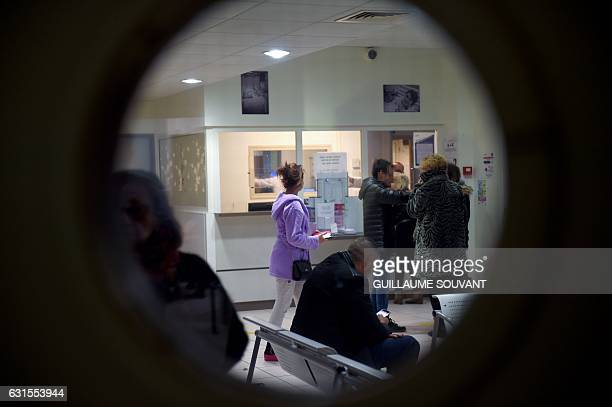 People wait at the reception of the emergency department of the hospital of Trousseau in Tours on January 12 during a major flu epidemic French...