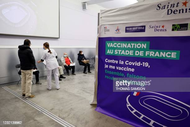 People wait before being vaccinated against Covid-19 at a vaccination centre set up at the Stade de France , in Saint-Denis, outside Paris on April...