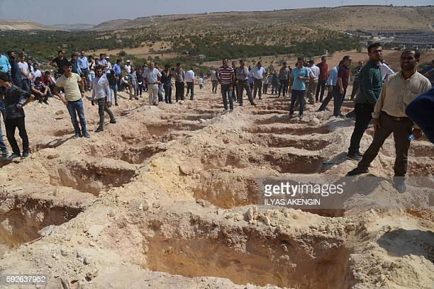 People wait close to empty graves at a cemetery during the funeral for the victims of last night's attack on a wedding party that left 50 dead in...